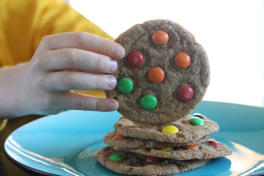 Child taking a soft M&M cookie. #glutenfree #vegan #dairyfree #recipe #cookie #glutenfreecookie #fairyflour