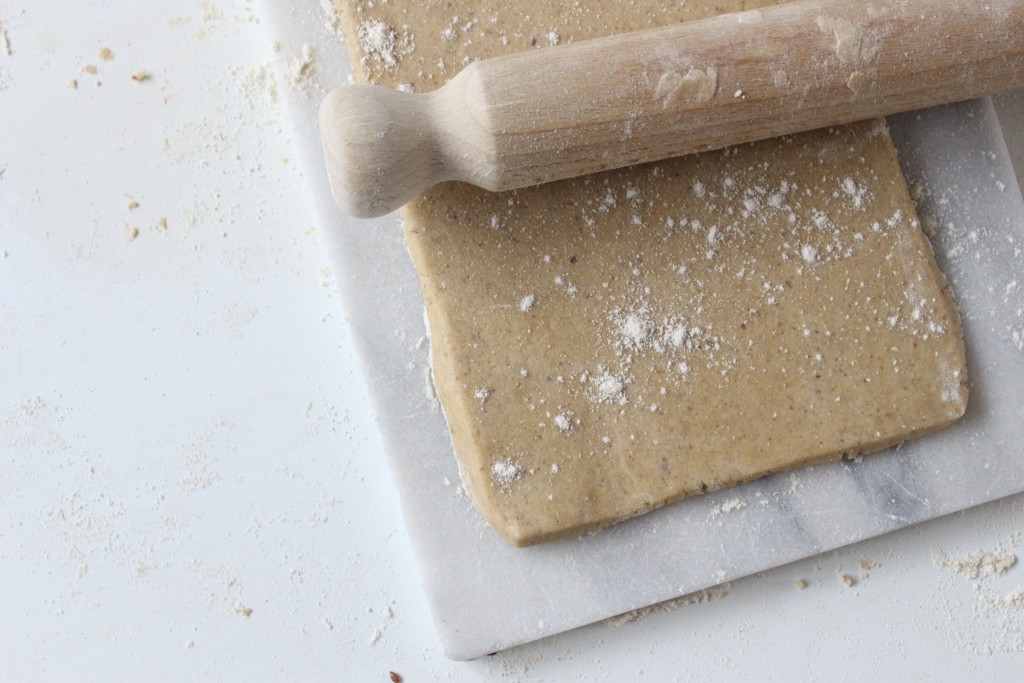 Overhead shot of gluten free pastry rolled out into a rectangle on a marble board. A wooden rolling pin is resting on top.