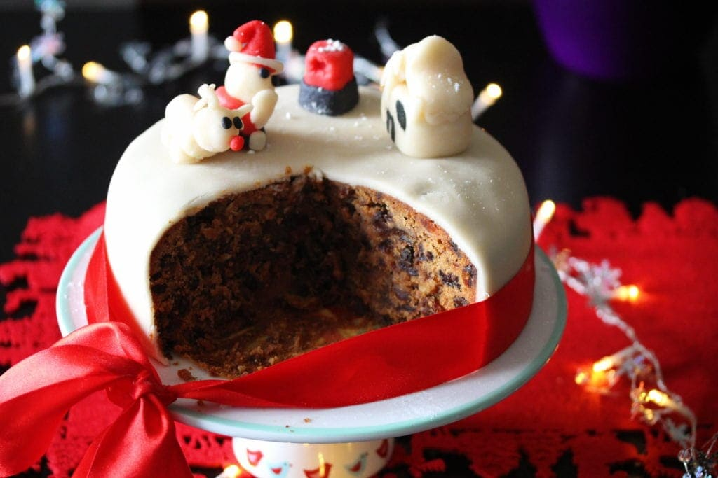An iced Gluten Free Christmas Cake on a stand and surrounded by festive decorations. Several slices have been removed to show the dark fruity interior of the cake.