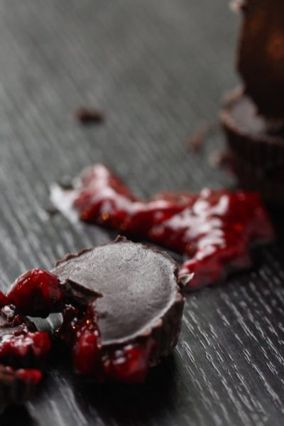 Raspberry sauce filled homemade chocolates. This simple recipe is perfect for halloween. Bite into the homemade refined sugar-free dark chocolate to find 'blood' inside!