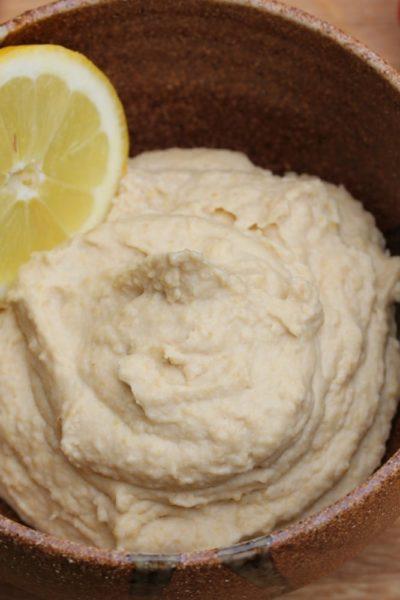 A bowl of lemon hummus with a slice of lemon