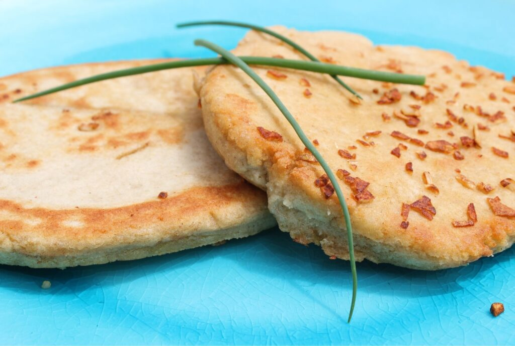 A side view of two gluten free garlic flatbreads on a blue plate. Crispy garlic pieces on top and on the plate.