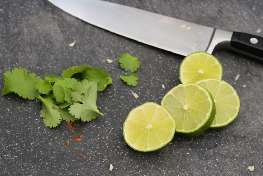Slices of lime and coriander ready for chopping with a large sharp knife on a black chopping board.