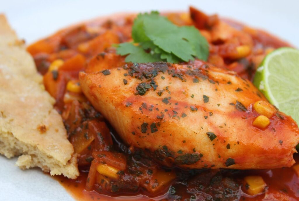 A fillet of fish in a spicy tomato sauce served with coriander and lime slice and a piece of garlic bread.