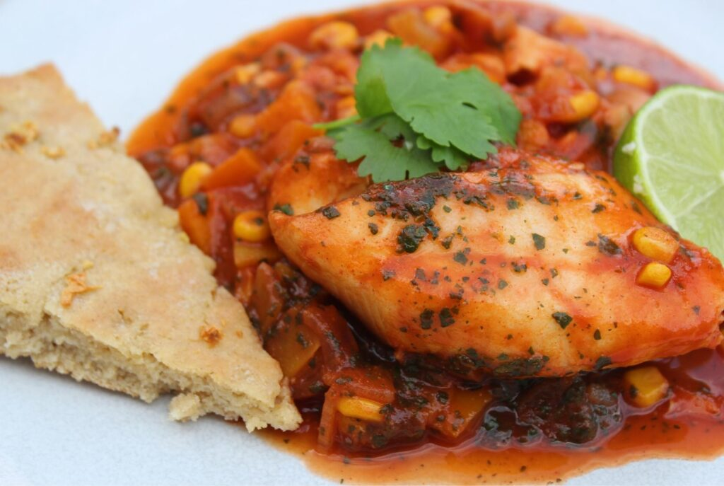 Moroccan fish - a spicy tomato sauce with frozen fish - served on a white place with a slice of garlic bread.