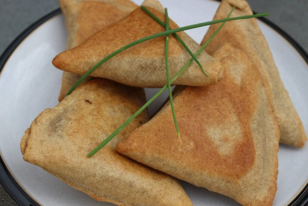 Gluten free samosas on a white plate with black rim, scattered with chives