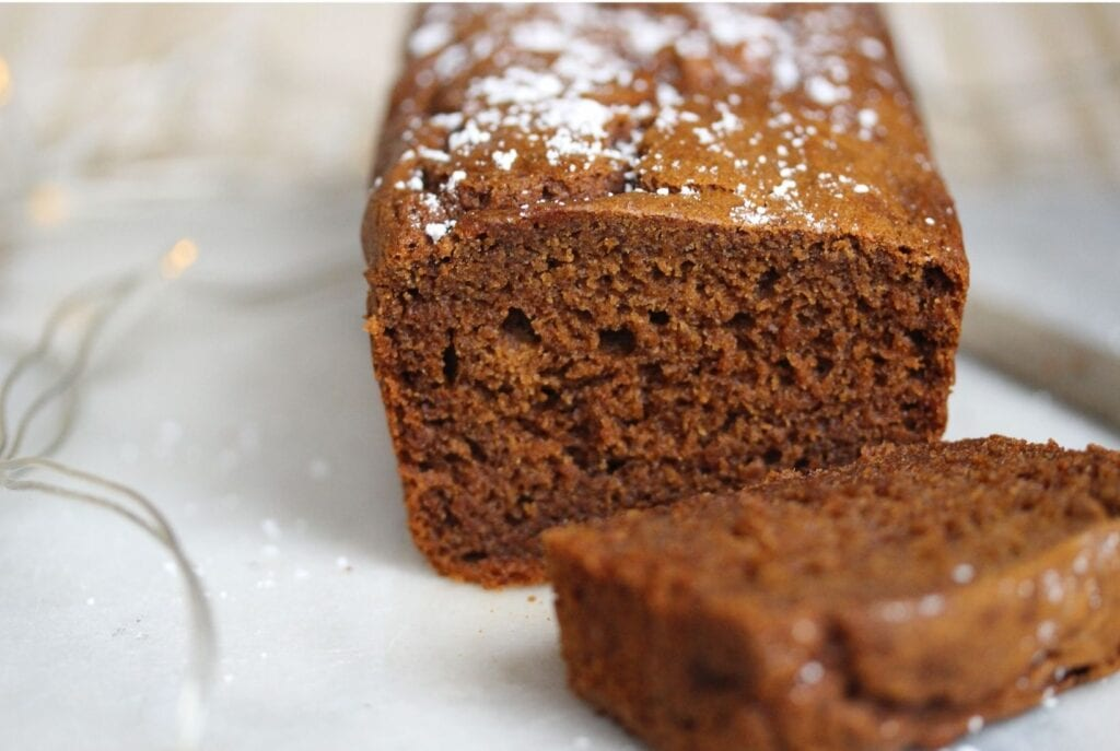 Gluten free gingerbread sliced open with a slice on one side and the whole cake on the other