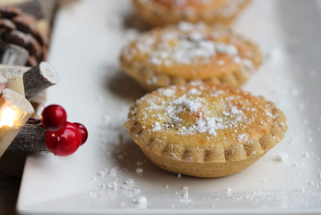 gluten free mince pies with a frangipane topping shown on a white plate with Christmas decorations to the left.