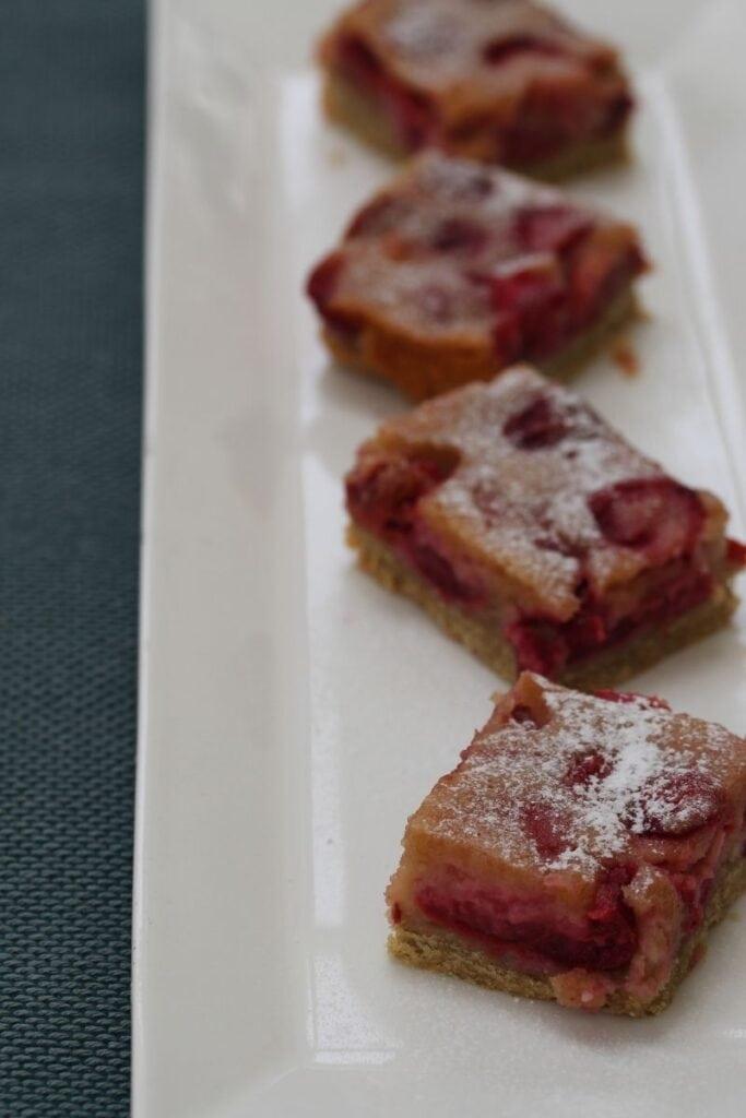 Slices of gluten free cherry pie on a white rectangular plate
